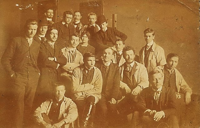 "Képzőművészeti főiskolás társaival (hátlapon felirat: ""Tökérián"" – baloldalon, karbafont kézzel, 1907) / Among fellow students at the Academy of Fine Arts (standing left, with arms crossed, 1907)"